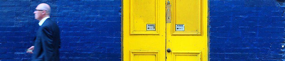 Blue brick wall and yellow door 948x205