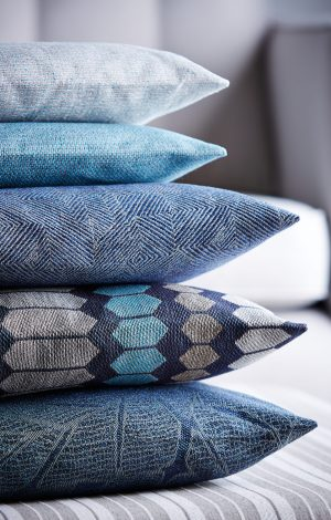 Shot of multi-colored pillows stack on ottoman stool