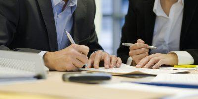 Executive signing paperwork, cropped